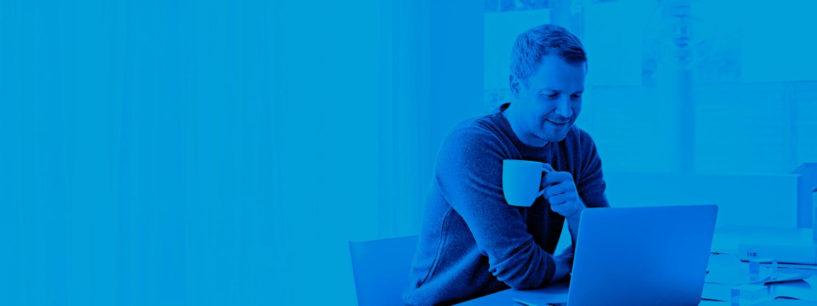 Photo d'un homme en train de boire du café pendant qu'il travaille